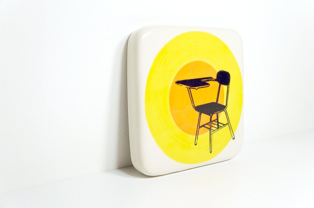tile of a school desk, perhaps in detention, on a color block of yellow and orange, made to order.