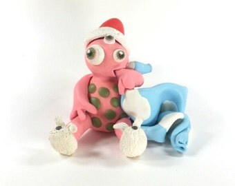 pink 3-eyed polymer clay monster wearing bunny slippers & cuddling a blue blanket