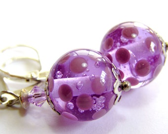 A pair of handmade lampwork earrings in lavender and sterling silver