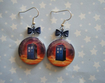 Tardis floating in space with blue bows dangle earrings on silver ear wires