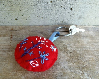 Red felt keychain with floral embroidery. Key ring for vegans in synthetic felt with embroidered flower. Stuffed keychain