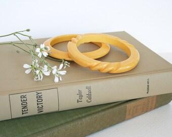 Two custard, creamed corn yellow bakelite bangles. Bracelets, carved, yellow, 1940s, stylish, summer, spring, fall.