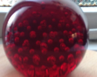 A Ruby red controlled bubble paperweight.