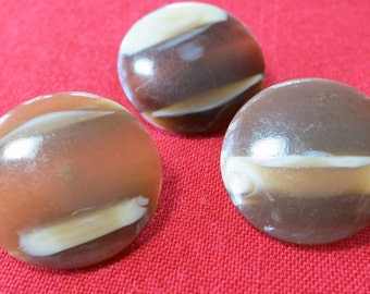 """3 Plastic buttons, 1"""" across, striped caramel, creamchocolate bands. Coat buttons, slightly dome front, metal loop back. UNK12.4-15.3-6.6."""