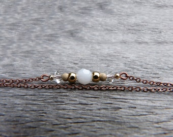 Bracelet on 2 thin copper chains, white Swarovski crystal, gold plated beads, transparent crystals, small glass bead and gold stardust beads