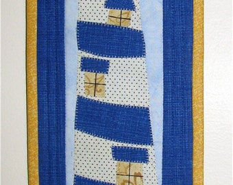 This is a handmade appliquéd and quilted wall hanging of a lighthouse in the harbor.