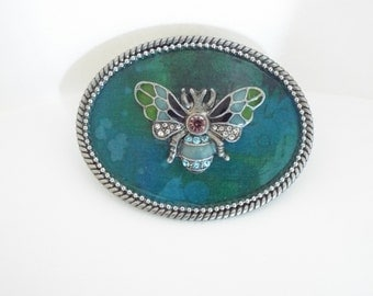 Antique Silver Buckle with blue background and rhinestone fly