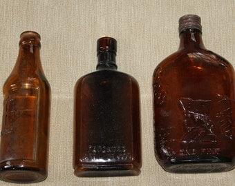 Lot of 3 Amber Bottles, 1 is a Measuring Bottle, 1 is a Medicine or apothecary Bottle & the third is a Liquor Bottle w a Face on it 1 pint.