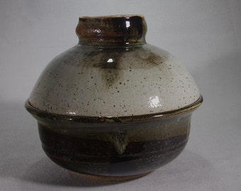 Large black, brown and white stoneware casserole with bowl lid.