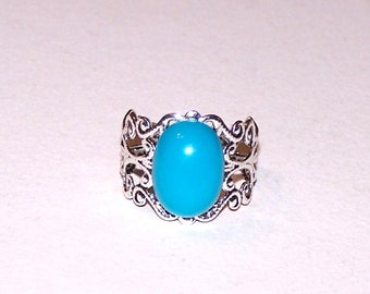 silvery filigree adjustable ring with blue cabochon