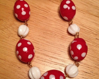 red, white polka dot, beaded necklace on a gold plated chain.