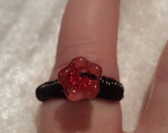Red and black wire wrapped pink flower ring with crystal in side.