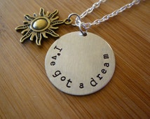 """Disney's TANGLED inspired necklace with bronze sun and """"I've got a dream"""" hand stamped on an aluminum circle"""