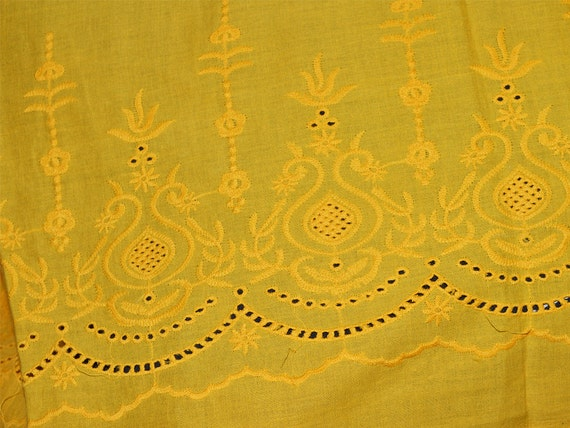 Yellow eyelet embroidered cotton fabric with border along one