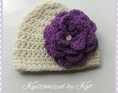 Crocheted cream colored baby beanie with oversized purple flower and pearl button in the center