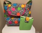 Diaper bag in black and white zebra print with pink yellow blue orange and green polka dots and  matching green changing pad