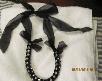 Whimsical black with crystals, tied up in bows, very cute!
