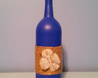 Handpainted dark blue wine bottle vase with decorative wrapping and handmade flower
