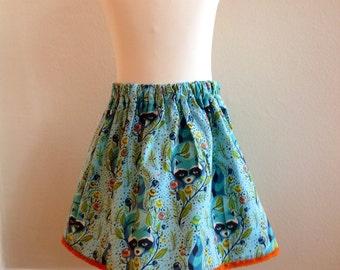 Girls skirt, turquoise raccoon design with orange lace trim