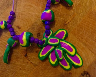 Multi coloured fimo necklace in purple, green and yellow details. Polymer clay, leather string, adjustable length. Bright and cheerful.
