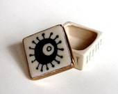 tiny porcelain box with silk screened retro pattern and bright gold luster
