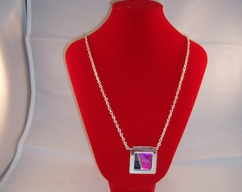 Dichroic glass necklace in a frame.
