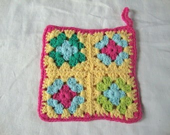 Handmade cotton Granny Square potholder in yellow, green, pink, and blue