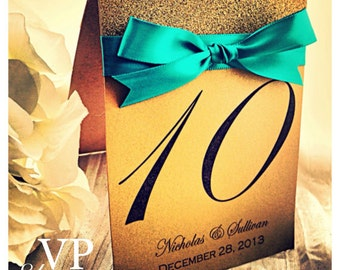 Gold table number with teal ribbon