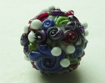 Focal glass lampwork bead with colorful flowers.
