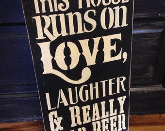 This house runs on love, laughter and really cold beer, sign