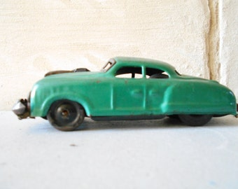 Mid century metal car toy , scale model toy car, with a gun.