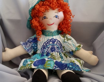 Old fashioned 15 inch cloth doll with red hair and blue eyes dressed in turquoise and white dress from the Ann Marie Collection