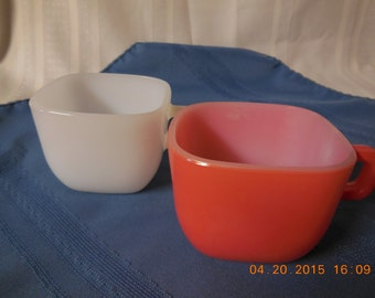 A pair of square glassbake cups one red one white from the 1960s.