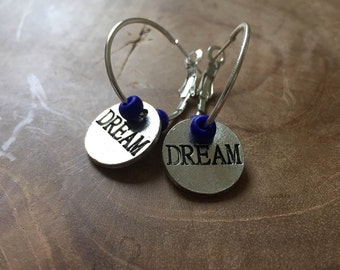 "DREAM: silvertone metal hoop earrings with cobalt blue glass beads and a round, silvertone metalen charm with ""DREAM"""