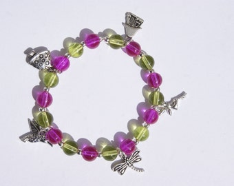 pink and green beaded bracelet with fairy, toadstool, bird, dragonfly and fairy house charms