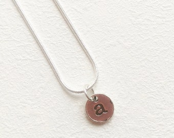 Cute initial letter-stamped pendant on silver plated chain.