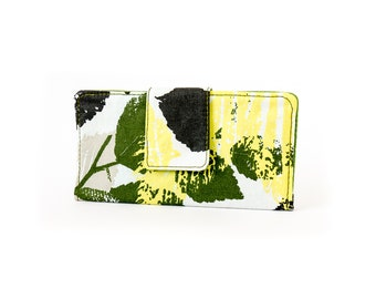 Two fold Wallet. Water resistant. Green foliage and white. 6 card slots, 2 wide slots, 2 zipper pockets.