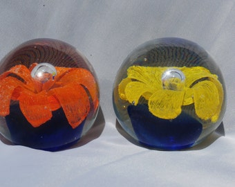 Pair of Glass Paperweights, Flower Design Inside, One Yellow and One Orange