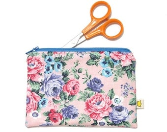 Pink zippered pouch with pink and blue flowers