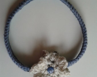Crochet headband with a ecru flower.