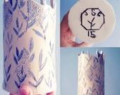Ceramic vase with a blue fern sgraffito design.