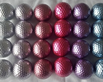 Set of six metallic, reflective Titelist golf balls in blue, purple, hot pink, mauve, pink and silver.