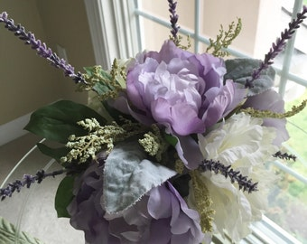 Spring arrangement with Light purple and white peonies in a silver vase