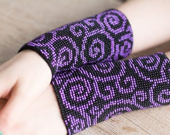 Hand-knitted black color wrist warmers decorated with purple/black beads