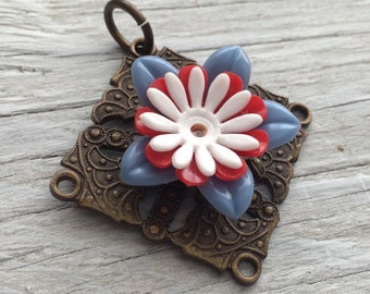 Antiqued brass pendant with red, blue and white flowers 45mm