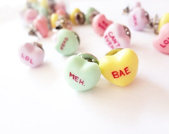 funny conversation hearts pins, bitter and sweet sayings in green, pink, yellow, and purple