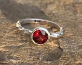 Sterling silver ring with bezel set round red garnet cut stone