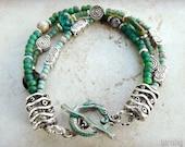 Multi strand beaded bracelet with hand painted mermaid clasp, ocean colors