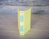 Pocket-sized notebook with lime green cover and teal stitching