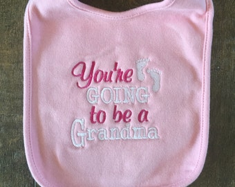 """Pregnancy Reveal Embroidered Baby Bib """"You're Going to be a Grandma"""" pink bib"""